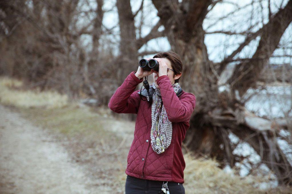 Femme observant la nature avec des jumelles 10x50